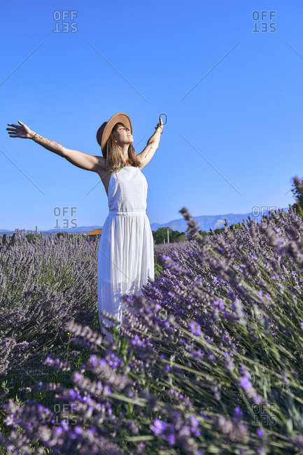Carefree woman with arms outstretched standing amidst lavender field against clear sky