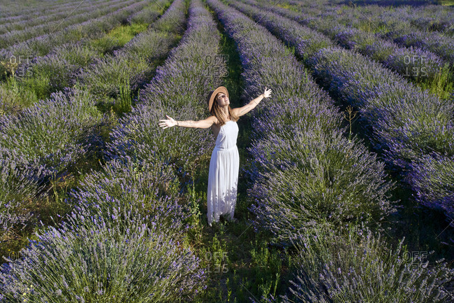 Woman wearing white dress with arms outstretched standing amidst lavender field
