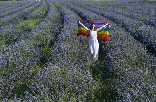 Woman wearing white dress holding rainbow flag while standing amidst lavenders