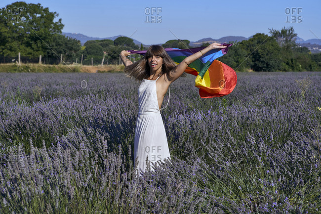 Mid adult woman holding rainbow flag while standing amidst lavender field