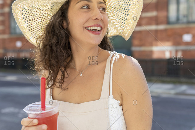 Close-up of happy young woman wearing hat holding drink in city