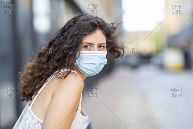Close-up of young woman wearing mask in city