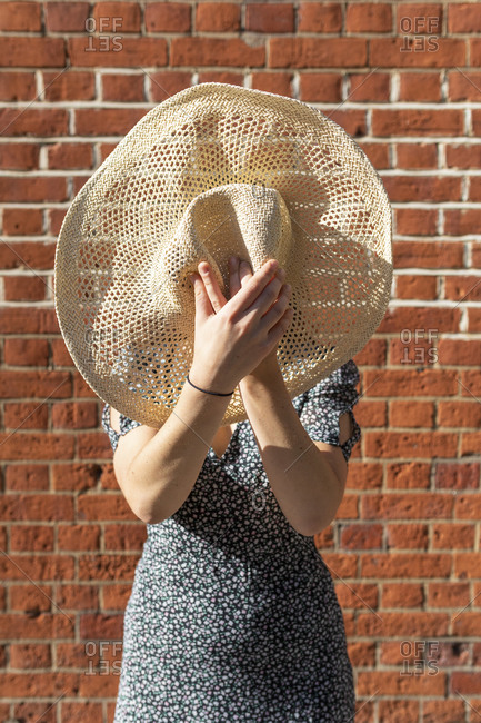 Young woman hiding behind straw hat while standing against brick wall during sunny day