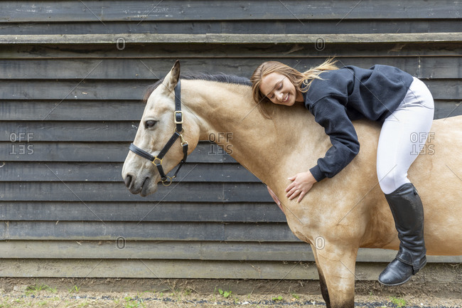 Young woman lying on the back of her horse