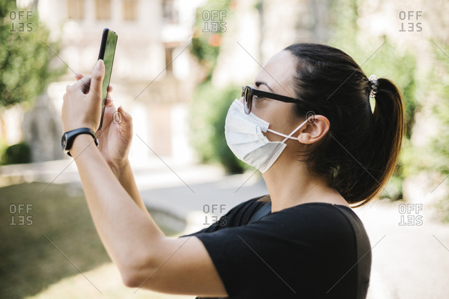 Woman wearing protective mask and taking a photo with her smartphone