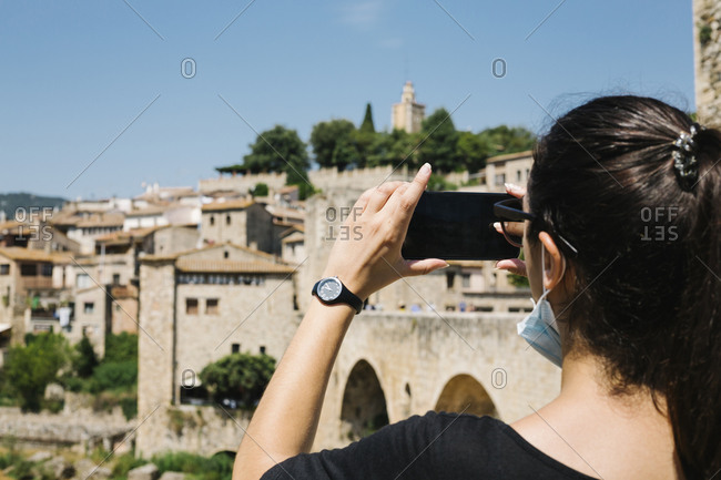 Woman wearing protective mask and taking a photo with her smartphone of Besalu- Catalonia- Spain
