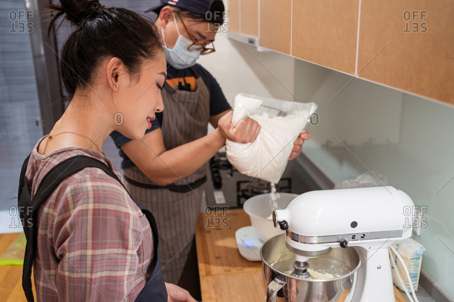 Young Asian man in mask weighing icing sugar while woman mixing butter in stand mixer