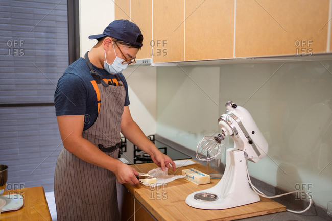 Young male baker in medical mask and apron cutting butter in pieces standing at counter with stand mixer
