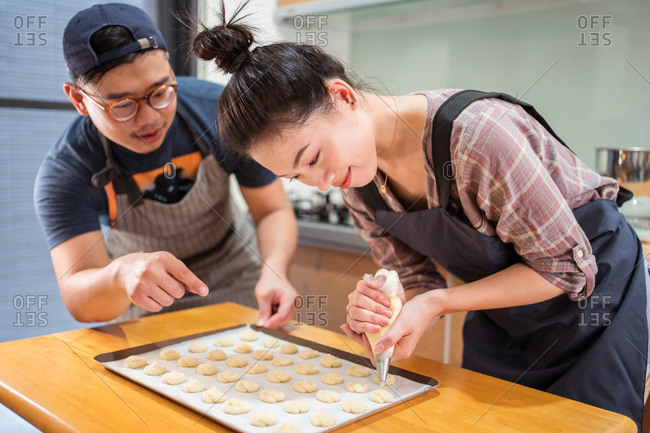 Asian guy helping smiling girlfriend with piping bag to pipe batter for pastries on baking pan at counter