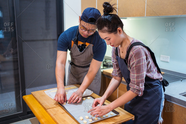 Young Asian man and woman in aprons working at home bakery and placing cookies on baking pan with parchment