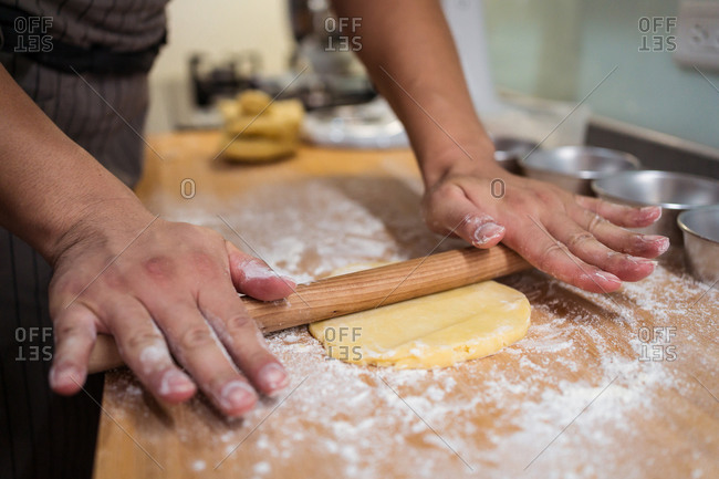 Cropped unrecognizable person in apron rolling dough with rolling pin working at home