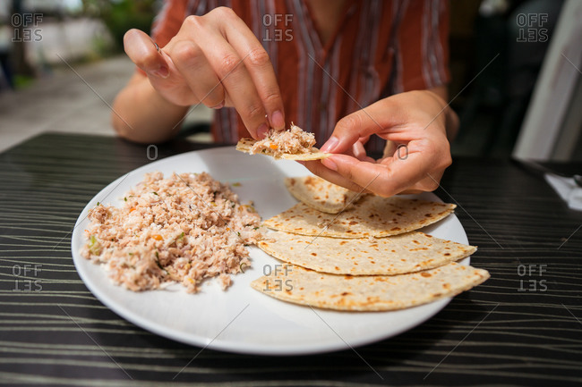Crop ethnic female enjoying delicious Mas Huni with chapati bread while sitting at table in restaurant during breakfast