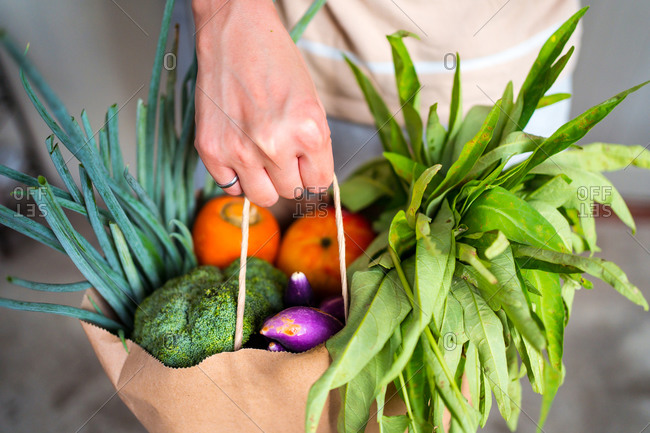 Unrecognizable crop female standing with paper bag full of ripe fruits and vegetables