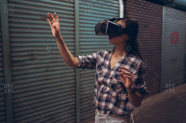 Calm female standing on narrow shabby street and experiencing virtual reality while wearing wireless VR goggles
