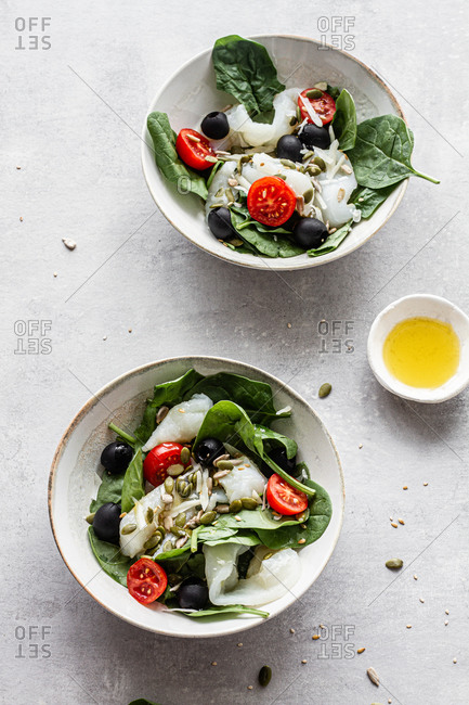 From above of bowls with delicious salad made with fish and green spinach with chopped cherry tomatoes and black olives garnished with seeds