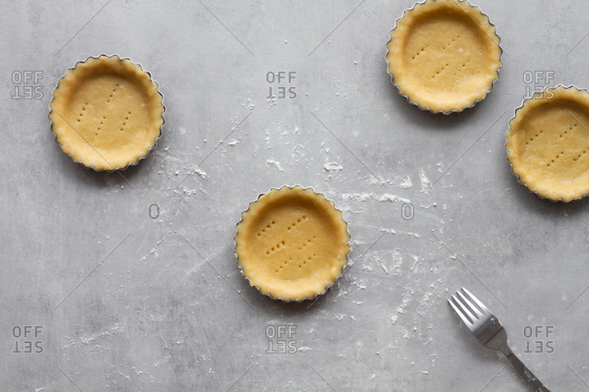 Top view of homemade short crust dough for lemon pie arranged in metal baking molds and perforated with fork ready for baking