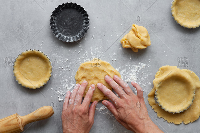 Top view of crop anonymous housewife filling metal forms with short crust pastry dough while preparing lemon pie in kitchen