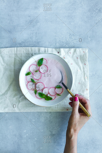 Top view of crop anonymous female eating delicious refreshing radish cream soup with fresh basil leaves