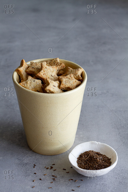 Appetizing homemade star shaped salted cookies with cumin seeds served in ceramic cup on marble table