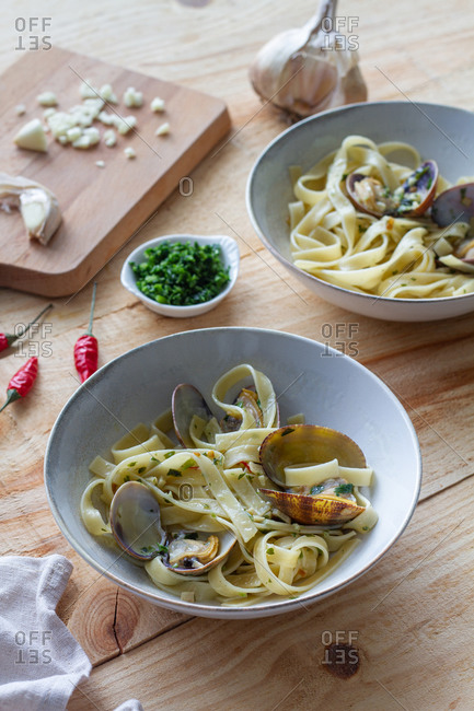 High angle of bowl of freshly cooked spaghetti with clams placed on wooden table in cafe