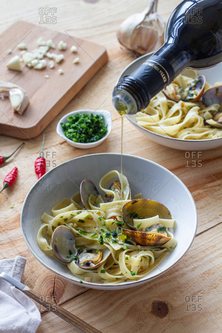 Unrecognizable cook pouring olive oil in bowl with spaghetti and clams placed on wooden table in restaurant