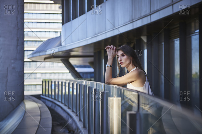 Side view of lonely pensive young female standing near glass border against contemporary urban building and looking away thoughtfully