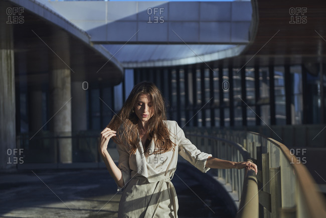 Lonely pensive young female standing near glass border against contemporary urban building
