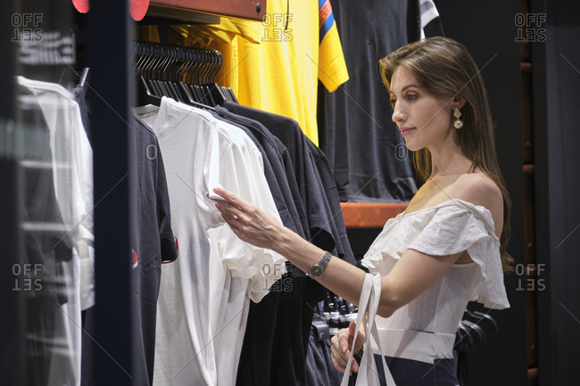 Side view of young stylish female standing near rack and choosing shirt while shopping in modern clothing store