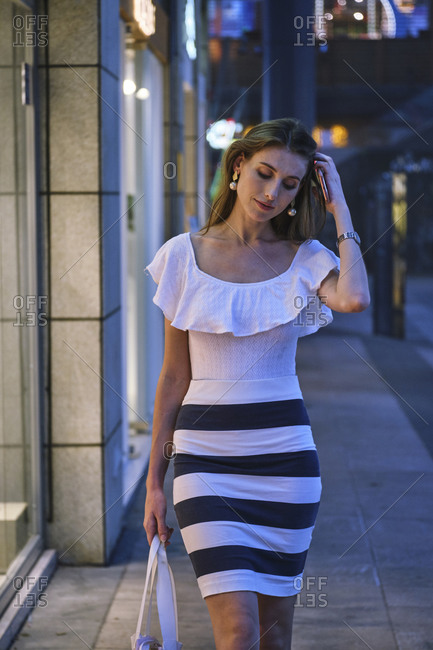 Low angle full body of young female in stylish dress and sneakers with bag in hand looking at shop windows while walking on city street and enjoying shopping time