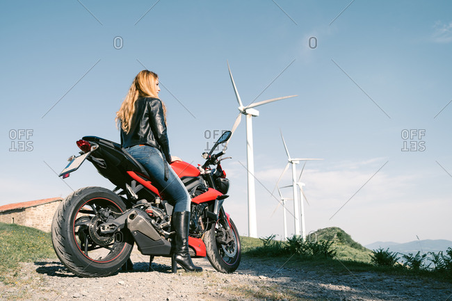 Side view low angle of brutal female biker sitting on motorbike on sandy road in summer and looking away