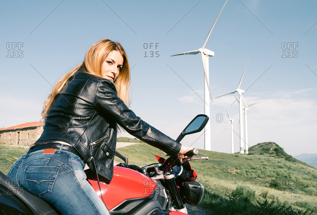 Side view low angle of brutal female biker sitting on motorbike on sandy road in summer and looking at camera