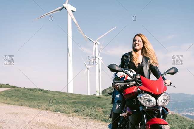 Female biker sitting on motorbike on sandy road in summer and looking at away