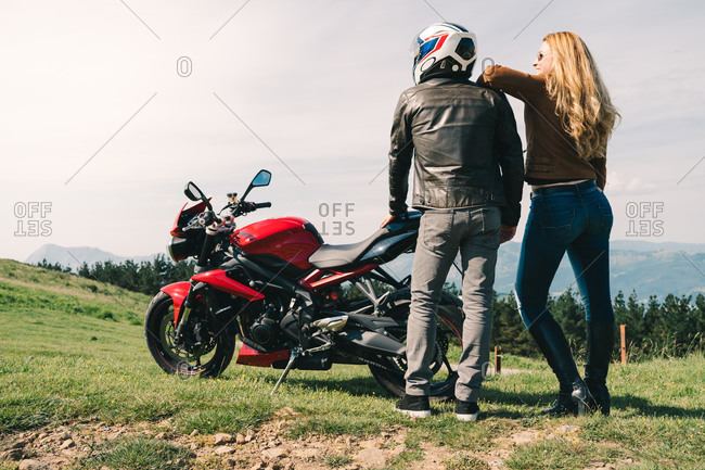 Back view of loving couple of motorcyclists standing together near modern motorbike and enjoying picturesque view of highlands