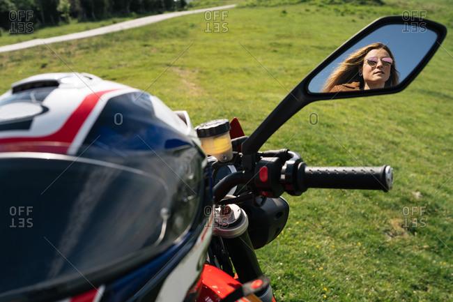 Female motorcyclist sitting on modern bike and enjoying amazing highland landscape on sunny day
