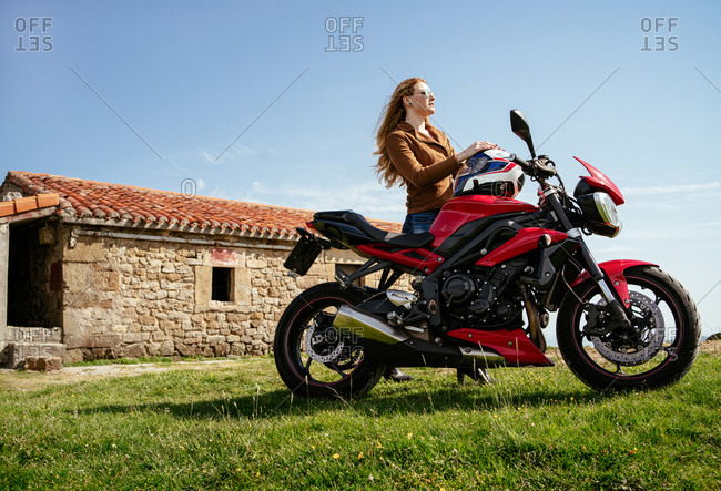 Side view low angle of brutal female biker standing near motorbike in summer and looking away