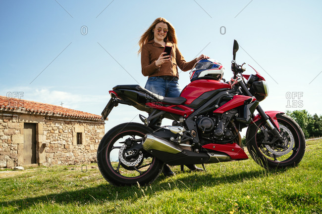 Low angle of delighted female motorcyclist standing near contemporary motorbike and browsing cellphone while enjoying weekend in countryside
