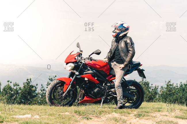 Determined male motorcyclist in helmet sitting on motorbike and enjoying freedom in mountainous area during weekend
