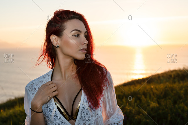 Alluring young red haired female in white translucent blouse looking away while standing on green meadow against calm sea during summer sunset