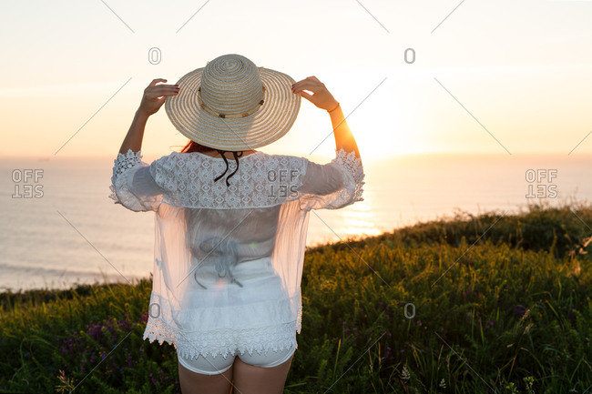 Back view of unrecognizable young female in stylish white clothes and straw hat standing on green hill and admiring sunset over sea in summer evening