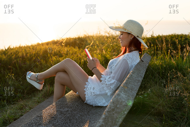 Side view of content young female in stylish summer outfit and hat sitting on stone bench and browsing mobile phone while resting on green meadow near sea in summer evening