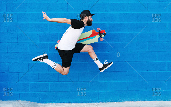 Side view of talented male skater with longboard in moment of jumping on background of blue wall in city
