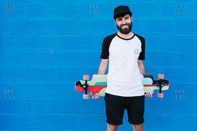 Cheerful male hipster with longboard standing near blue brick wall and looking at camera during city stroll