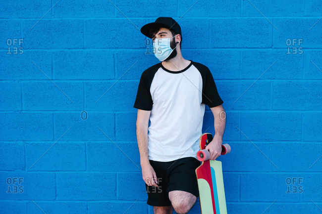 Young male hipster with longboard and in protective mask standing in city near blue brick wall and looking away during coronavirus epidemic