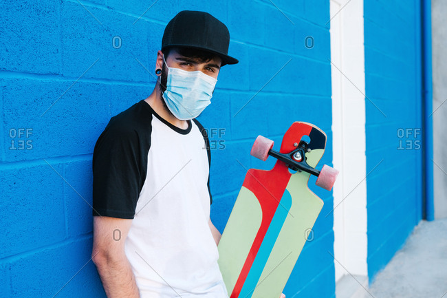 Young male hipster with longboard and in protective mask standing in city near blue brick wall and looking at camera during coronavirus epidemic