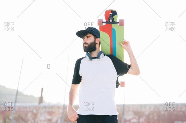 Low angle of male hipster standing with longboard and enjoying weekend in city on summer day