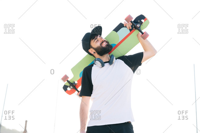 Low angle of happy male hipster standing with longboard and enjoying weekend in city on summer day