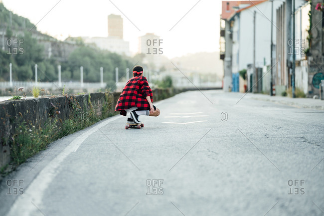 Back view of male hipster in checkered shirt riding longboard along asphalt road while entertaining during weekend in city