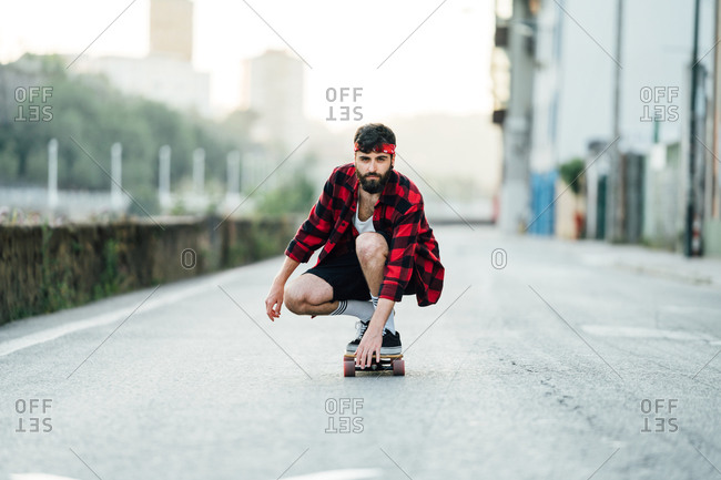 Male hipster in plaid shirt sitting on longboard and riding along road