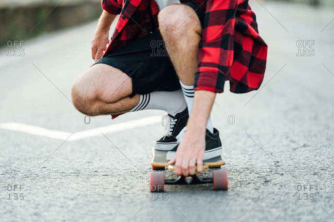 Unrecognizable male hipster in plaid shirt sitting on longboard and riding along road