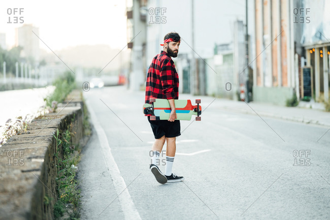 Back view of male skater in checkered shirt and with longboard walking along asphalt road while relaxing during summer weekend in city